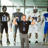 A guest flexing his biceps, posing in front four mannequins wearing jerseys at the Jamie Hosford Football Center dedication.